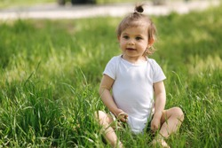 Happy little girl sits on the grass outdoors. Cute baby girl in white bodysuit and sunglasses on the backyard. Adorable kid play with grass