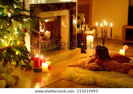 Happy Little Girl Sitting By A Fireplace In A Cozy Dark