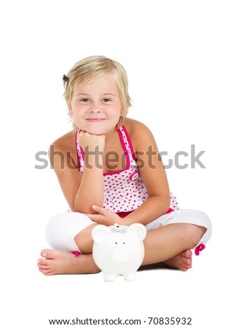 happy little girl sitting on floor with piggy bank