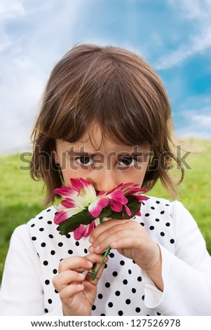 Happy little girl smelling flowers in his hand against the blue sky - stock photo