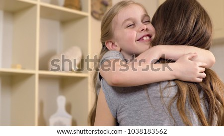 Happy little girl smiling and hugging mother with love, warm childhood memories