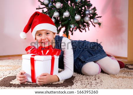 Happy little girl smiling with gift box near the Christmas tree. - stock photo