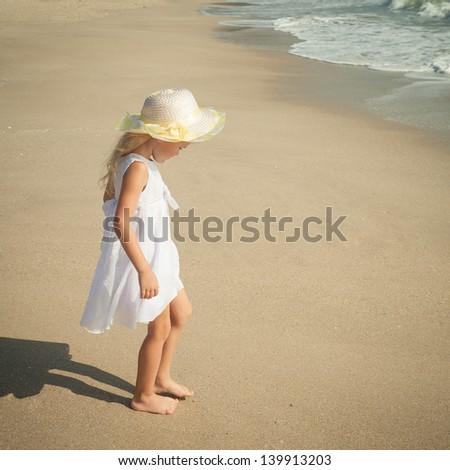 happy little girl standing on beach