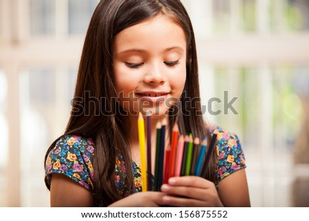 Happy little girl trying to decide which color to use on one of her drawings