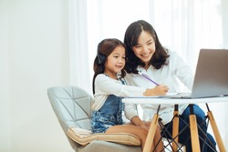 happy Little girl wear headphone study online with video call teacher with her mother
