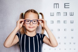 Happy little girl wearing glasses taking eyesight test before school with blurry eye chart at the background, child's vision examination