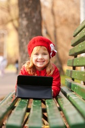 Happy little girl wearing red with tablet pc on bench in the park.