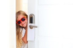 Happy little girl wearing sunglasses in hotel room opening the door. Family vacation concept