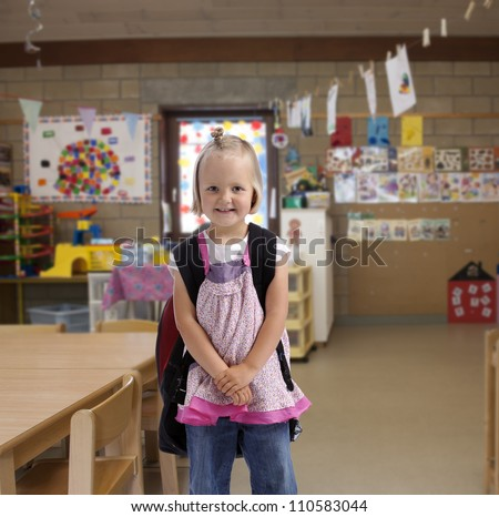 happy little girl with bag pack in a classroom. isolated on white background