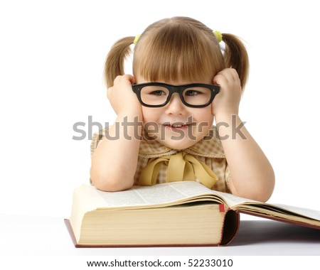 Happy little girl with big book wearing black glasses, back to school concept, isolated over white