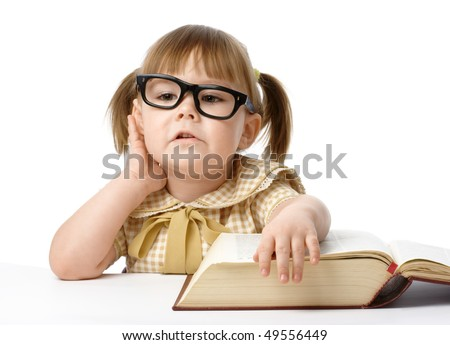 Happy little girl with big book wearing black glasses, isolated over white