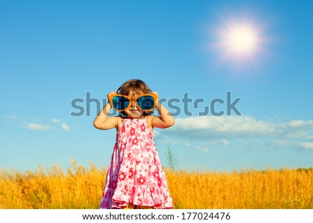 Happy little girl with big sunglasses in the wheat field