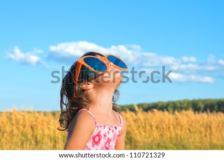 Happy little girl with big sunglasses looking at the sky
