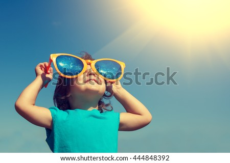 Happy little girl with big sunglasses  looking at the sun #444848392