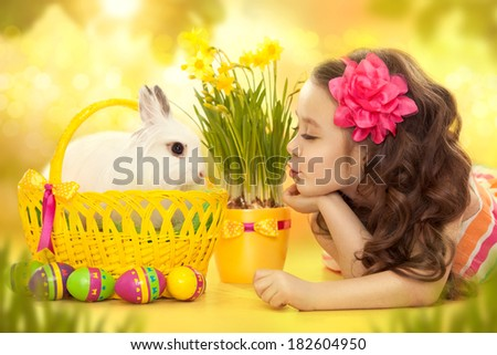 Happy little girl with easter rabbit in basket and eggs. Greeting card