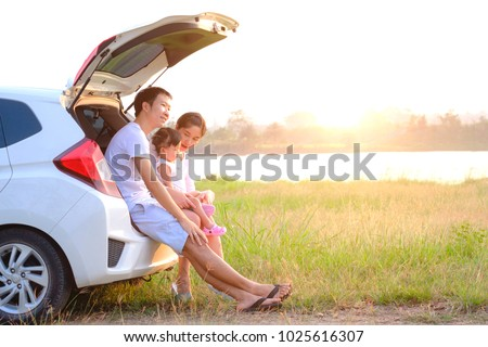 happy little girl with family sitting in the car.Car insurance concept