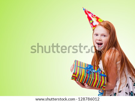 happy little girl with gift box on green   background