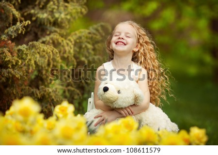 Happy little girl with her bear toy in blooming garden