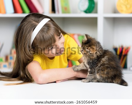 Happy little girl with her kitten at home at home