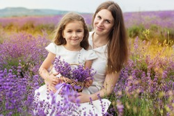 Happy little girl with her mother are in a lavender field holding bouquet of purple flowers