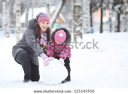 happy little girl with her mother rolled lumps of snow, make a snowman