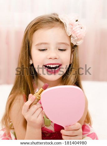 Happy little girl with lipstick and  mirror