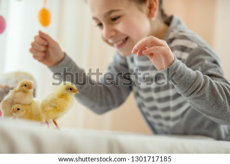 Happy little girl with little chickens on easter decor background. Joyful emotions girls.