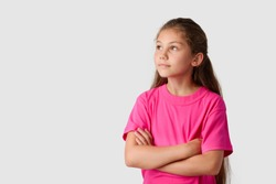 Happy little girl with natural long hair keeps hands crossed and looking left and up. Adorable young female wears pink T-shirt is happy and in high spirit
