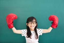 happy little girl with red boxing gloves before chalkboard