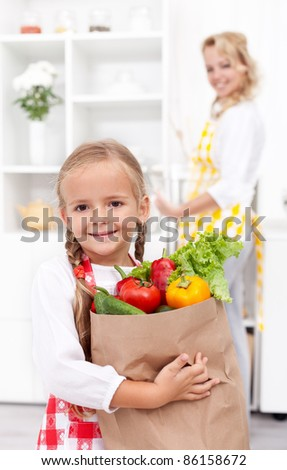 Happy little girl with the groceries bag in the kitchen