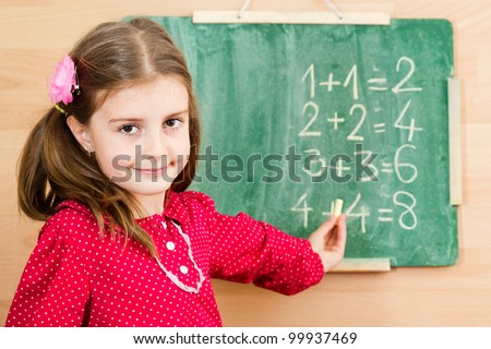 Happy little girl writing on blackboard