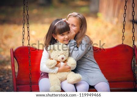 Happy little girlfriends on swing in park