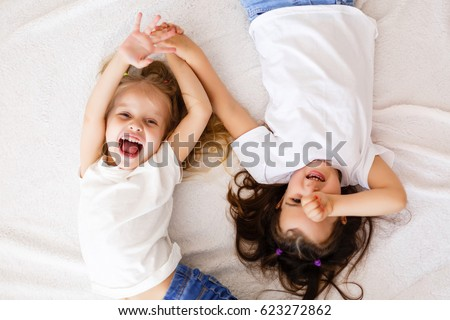 happy little girls lying on back top view sisters stock photo