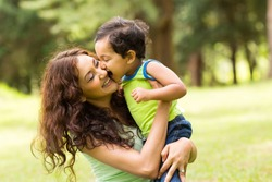happy little indian boy kissing mother outdoors