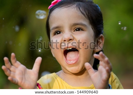 happy little Indian girl playing with bubbles