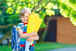 Happy little kid boy in colorful shirt and backpack or satchel and traditional German school bag cone called Schultuete with gifts on his first day to school. Child outdoors on warm sunny day.