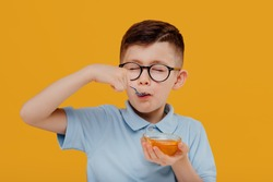 Happy little kid boy in glasses smiling and eating fresh liquid honey from bowl against yellow background