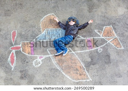 Happy little kid boy in pilot uniform having fun with airplane picture drawing with colorful chalk. Creative leisure for children outdoors in summer. #269500289