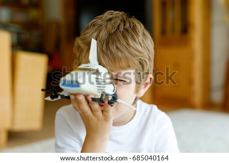 Stock Photo Happy little kid boy playing with space shuttle toy. Cute child in having fun in the morning before school. Closeup of face and old toy