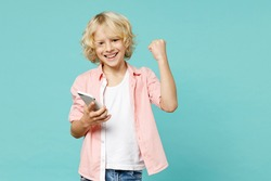 Happy little kid boy 10s wearing pink shirt using mobile cell phone typing sms message doing winner gesture isolated on blue turquoise background children studio portrait. Childhood lifestyle concept