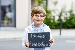 Happy little kid boy with backpack or satchel and glasses. Schoolkid on the way to school. Healthy adorable child outdoors On desk Bye elementary school in German. School's out