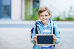 Happy little kid boy with backpack or satchel and glasses. Schoolkid on the way to school. Healthy adorable child outdoors On desk Last day third grade in German. School's out