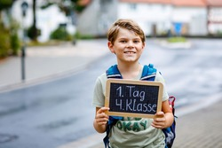 Happy little kid boy with backpack or satchel. Schoolkid on the way to middle or high school. Child outdoors on the street. Back to school. On desk First day fourth grade in German.