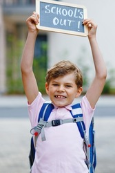 Happy little kid boy with backpack or satchel. Schoolkid on the way to school. Healthy adorable child outdoors With chalk desk for copyspace. Back to school or school's out.