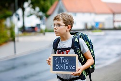 Happy little kid boy with glasses and backpack or satchel. Schoolkid on the way to middle or high school. Child outdoors on the street. Back to school. On desk First day fifth grade in German.