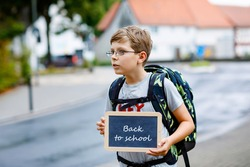 Happy little kid boy with glasses and backpack or satchel. Schoolkid on the way to middle or high school. Child outdoors on the street. Back to school. Kid holding chalk desk