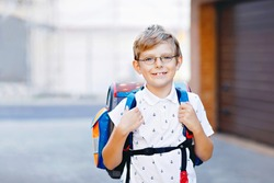 Happy little kid boy with glasses and backpack or satchel. Schoolkid on the way to school. Portrait of healthy adorable child outdoors. Student, pupil, back to school. Elementary school age
