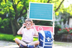 Happy little kid boy with glasses sitting by desk and backpack or satchel. Schoolkid with traditional German school bag called Schultuete on his first day to school. Back to school