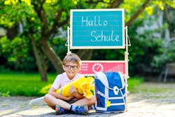 Happy little kid boy with glasses sitting by desk and backpack satchel. Schoolkid with traditional German school bag cone called Schultuete on his first day to school.Hello school in German language