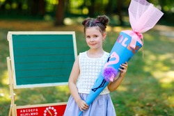 Happy little kid girl by desk with backpack or satchel and big school bag or cone traditional in Germany for the first day of school. Healthy adorable child outdoors, in green park. Copyspace on desk.